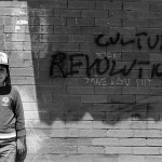 little boy standing in front of a brick wall with words Culture Revolution spray painted on it
