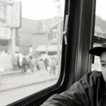 Adolescent boy sitting in street car with baseball hat that says Six Nations