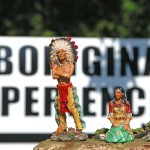 Toy figurines of Indian couple in traditional attire foreground, sign saying Aboriginal Experiences in background, outside