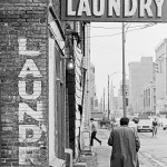 City buildings with sign reading Kam Lee Laundry and the body of a man walking away