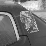 detail shot of the back window of a car, the words Matador and sticker of a Indian Chief in headdress on the car