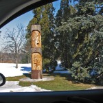 shot from the window of a car of a wooden pole carved with the profiles of two traditionally dressed Indian men, snow, grass and evergreen trees surronding the carving