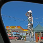 shot framed from a car window, large wooden carving of a statue of an Indian man in traditonal attire and headdress in front of gas station