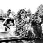 Group of mostly male powwow dancers standing in the back of a pickup truck as it drives away