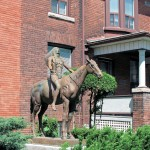 Statue of Indian man in traditional dress on a horse, arms outstretched and face looking upwards, in background brick house in a city neighbourhood
