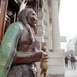 Wooden statue of a cigar store Indian, another one behind him, street scene with people walking and classical architecture with columns in the background