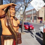 Wooden cigar store Indian standing on urban street scene with parked cars in the background