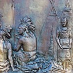 Metal frieze of scene of two Indian men in traditional attire and a woman in front of two teepees