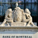 Stone carving in front of wrought iron grilles and glass window, carving of two men, one an Indian man in traditional attire, a beaver and an owl stand the crest between them, underneath the words Bank of Montreal are carved
