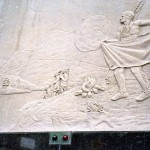 Stone carving frieze with scene of Indian man in traditional dress and campfire in front of him