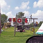 part of a car side view mirror in foreground, in background decorated shields hanging off wooden poles and a teepee