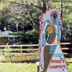 wooden cutout of Indian figure with headdress and hole for someone to put their face in, sign on the cutout reads Gifts and Ryan's Campsite