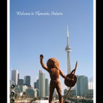 Toy figurine of Indian man in headdress and holding a shield and spear in foreground, urban cityscape with CN Tower in the background