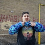 teenage boy standing in front of brick wall with the words Nanabush Rules spray painted on it and lifting up his shirt to show a t-shirt with a traditionally dressed Indian man on the front
