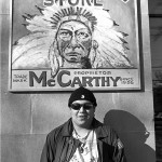 Teenage boy in front of a painted billboard that reads General Store and has a man in traditional Indian headdress painted on it