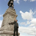 young man standing in front of a large monument with statue of man dressed in traditional French attire. The young man is holding a GPS metre.