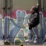 Young man with headphones on hanging off of a railway car that is painted with graffiti.