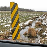 a barren farmer's field in the winter, covered in some snow and a small river running through. A sideview mirror of a car where you can see the reflection of a young man stranding.