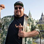 Young man standing with right arm raised in fist and other arm holding a plastic figurine of an action figure dressed as a traditional Indian. In the background are the Parliament Buildings of Canada