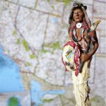 Toy figurine of traditionally dressed Indian man in foreground, map of Western American in the background