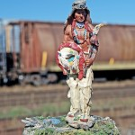 Toy figurine of traditionally dressed Indian man in foreground, railway car in background