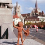 Toy figurine of Indian man in headdress and holding a shield and spear in foreground, building with regal European architecture in background