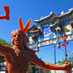 Toy figurine of Indian warrior man holding tomahawk in foreground, elaborate traditional Chinese style arch in background