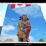 Toy figurine of Indian man in traditional dress and wrapped in red robe in foreground, glass office building with Canadian Flag draped on it in background
