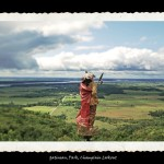 Toy figurine of Indian man in traditional dress and wrapped in red robe on a hill in foreground looking out over grassy vallery and cloudy sky