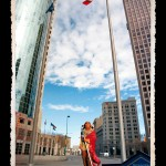 Toy figurine of Indian man in traditional dress and wrapped in red robe in foreground, street scene of tall glass skyscrapers and pole with Canadian flag in background