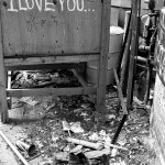 a back alley with wood bits, garbage, old pair of shoes and a cabinet with the words If you don't love me I love you spray painted on it.