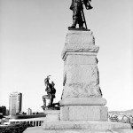 Large monument with two metal sculptures, one of Samuel de Champlain dressed in traditional French attire and below a kneeling man dressed in traditional Indian attire