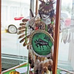 figure in window of hotel lobby, dressed with traditional powwow dancer attire