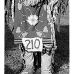 image of the legs of a powwow dancer in traditional attire with his number 210 attached to his outfit