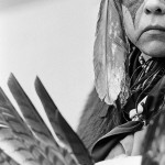 Close up face shot of older aboriginal man dressed in traditional dress for powwow