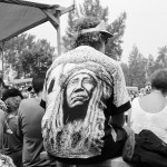 Audience onlookers at a powwow, one man is wearing a t-shirt which on the back is printed the face of a man in traditional Indian attire