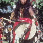 Young aboriginal man dressed in traditional dress and performing at a powwow