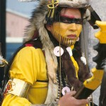 Headshot of young aboriginal man dressed in traditional dress for powwow