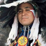 Headshot of middle aged aboriginal man dressed in traditional dress for powwow