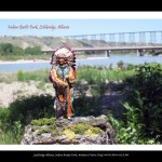 Toy figurine of Indian man in traditional attire in foreground, river, bridges and rocks in background