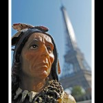 Upclose shot of the head of a toy figurine of a man in traditional Indian attire in foreground with Eiffel Tower in background